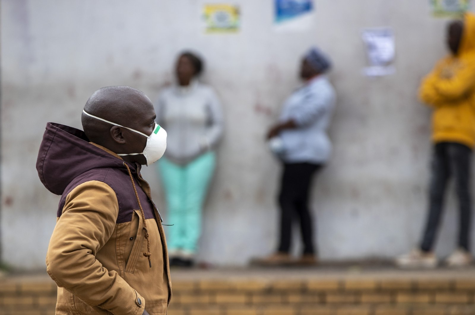 A man wearing a face mask to protect himself against the coronavirus walks past people queuing for shopping in Duduza, east of Johannesburg, South Africa, April 2, 2020. South Africa went into a nationwide lockdown for 21 days in an effort to mitigate the spread to the coronavirus. (AP Photo)