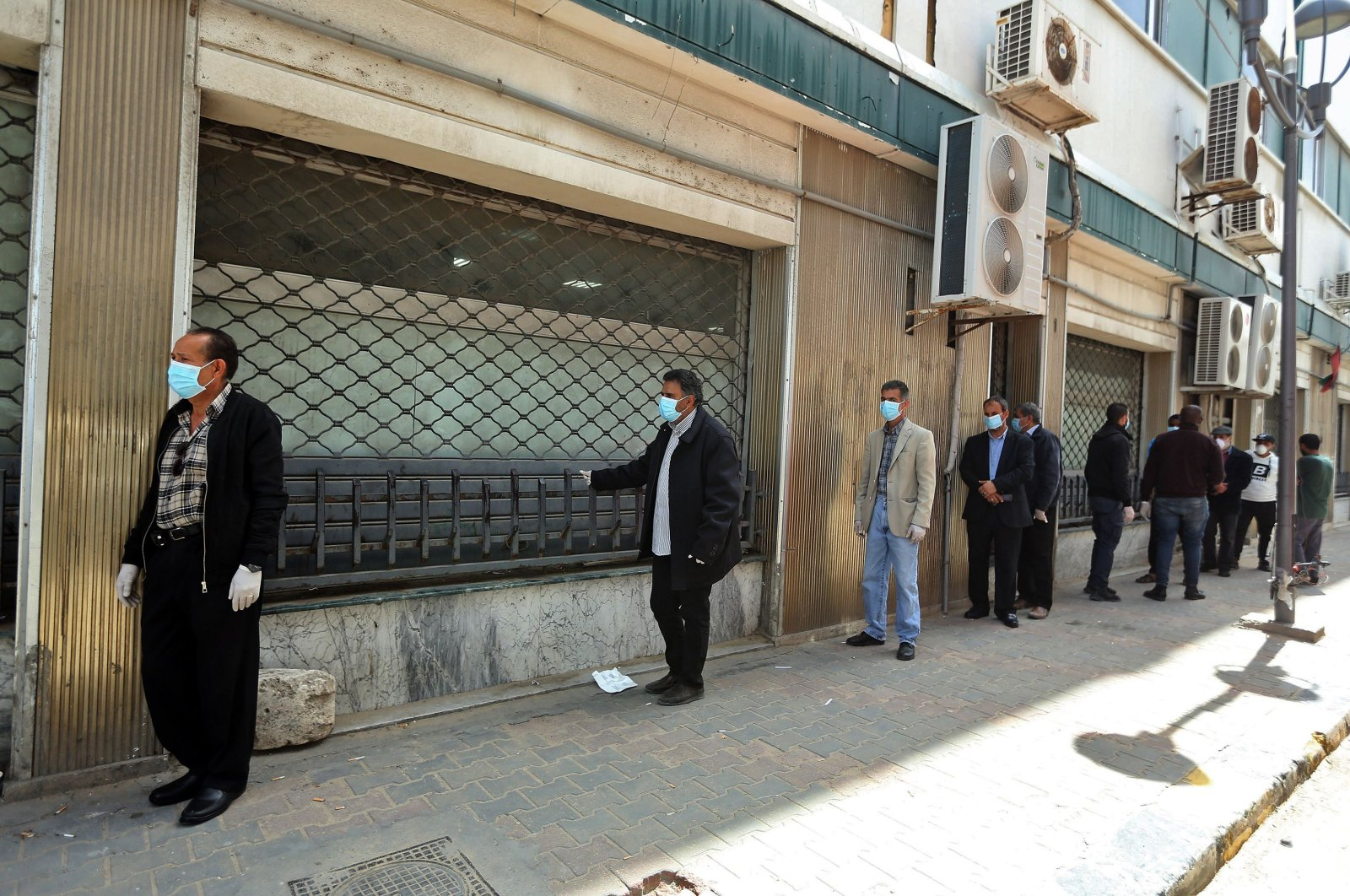 Libyans wearing protective face masks queue in front of a bank in the centre of the capital Tripoli on April 1, 2020, amidst the novel coronavirus pandemic crisis. (AFP Photo)