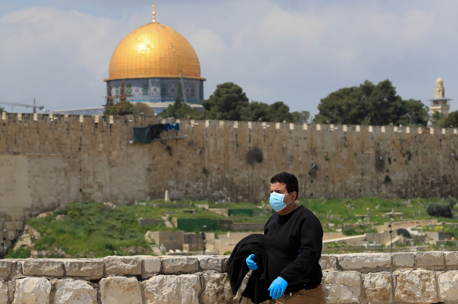 A man wearing a mask and gloves walks past the Dome of the Rock mosqu in Jerusalem's Old City on April 2, 2020. (Photo by Emmanuel DUNAND / AFP)