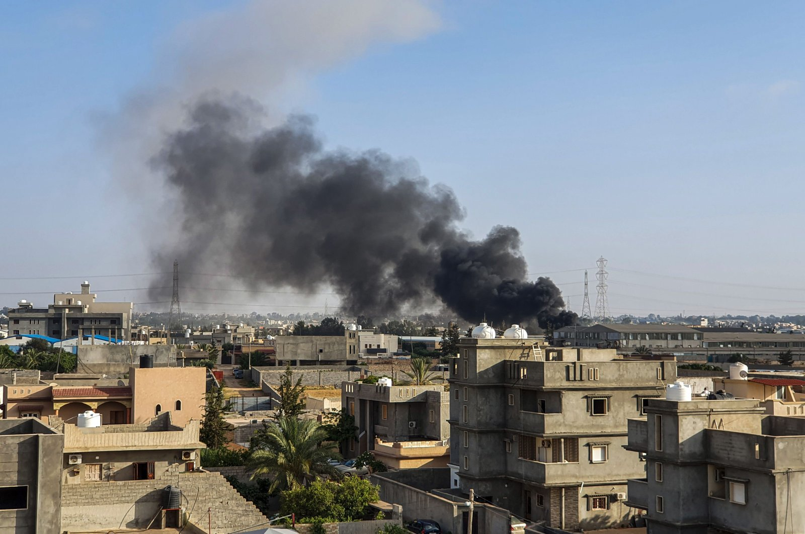 This picture taken on June 29, 2019, shows smoke plumes rising in Tajoura, south of the Libyan capital Tripoli, following a reported airstrike by forces loyal to warlord Gen. Khalifa Haftar. (AFP Photo)