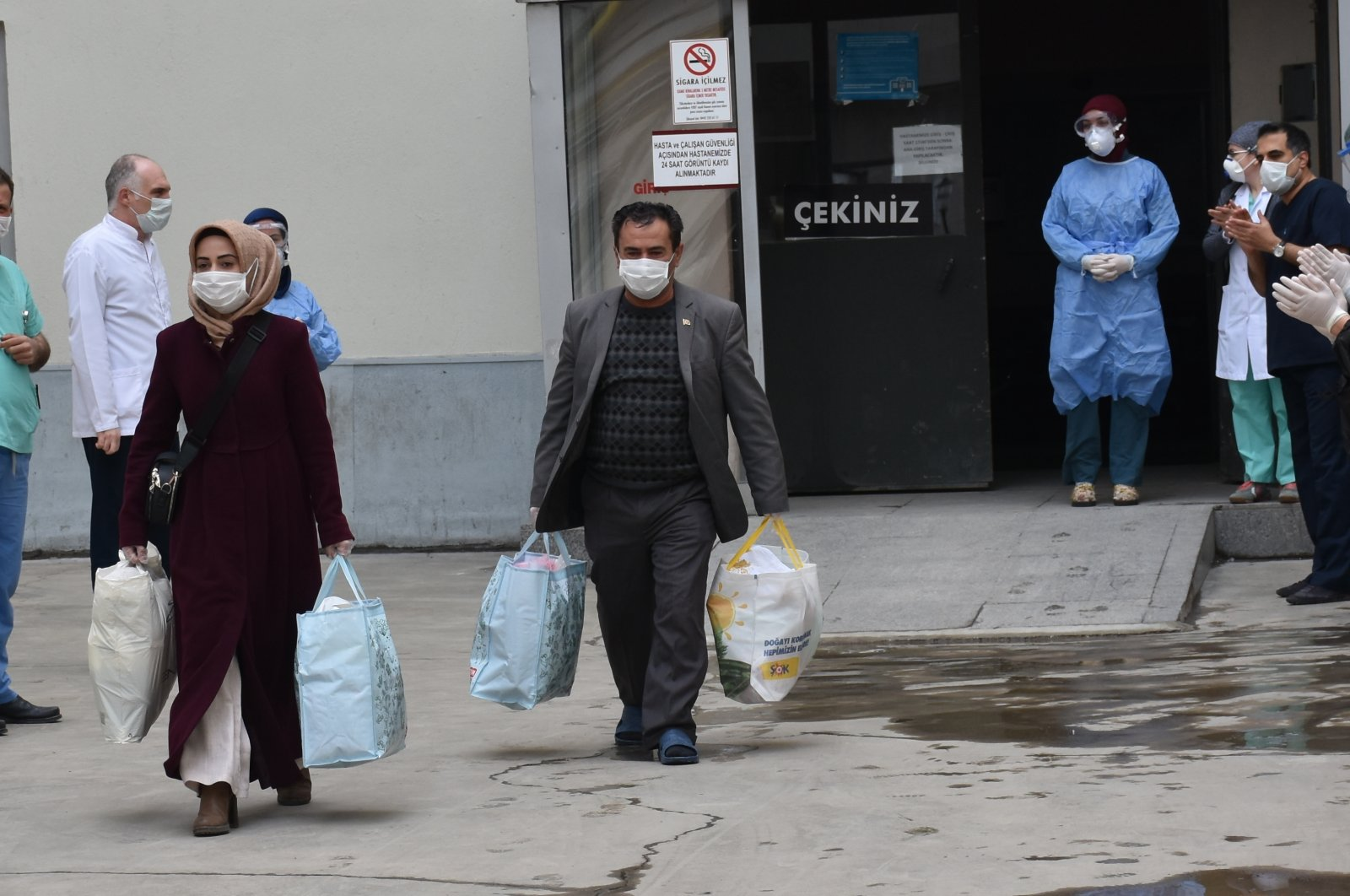 Nurses and doctors wave goodbye to two patients who were discharged from the hospital after they recovered from COVID-19, Erzurum, Saturday, March 4, 2020. (AA Photo)