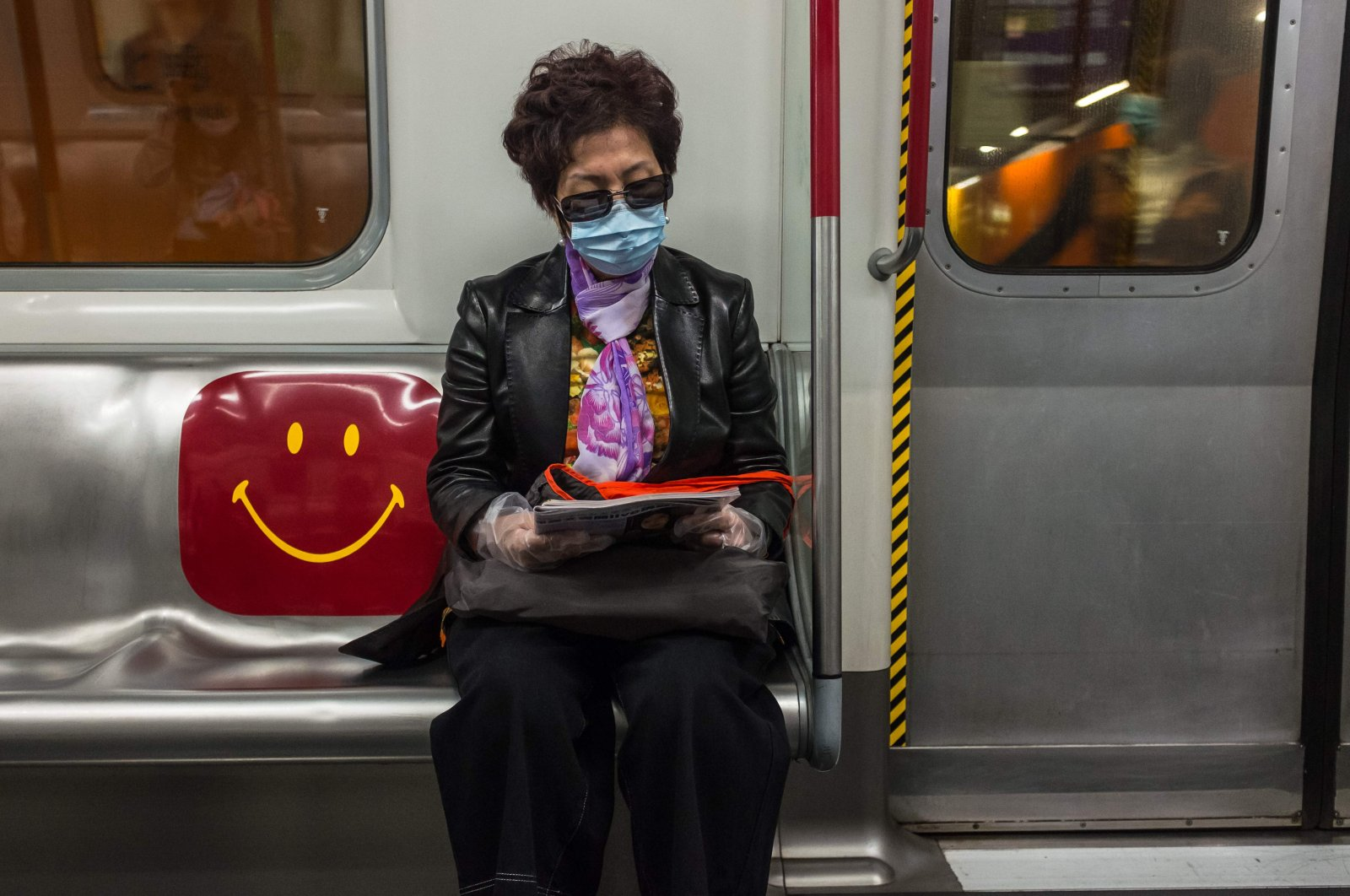 A woman wearing a face mask amid concerns of the COVID-19 pandemic commutes on a train in Hong Kong, Saturday, April 4, 2020. (AFP Photo)