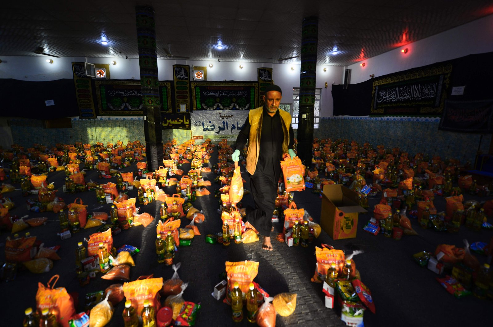 A man sorts donations for families in need during the COVID-19 pandemic in the holy city of Najaf, Iraq on March 25, 2020 (AFP Photo)