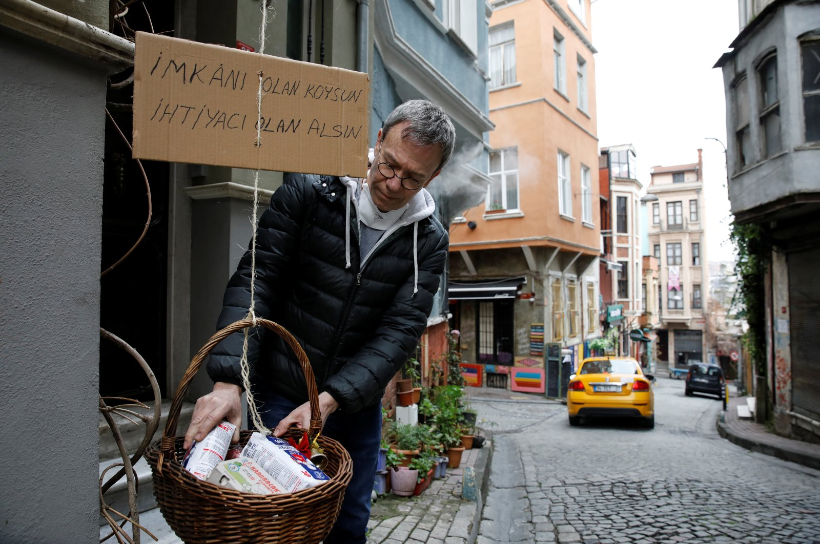 """Jeffrey Tucker adds items to a basket he lowered from his window as a sign of social solidarity with poor and homeless people in need amid the coronavirus outbreak in Istanbul, Turkey, April 3, 2020. The cardboard reads, """"Those who have the means, add. Those who need, take."""" (Reuters Photo)"""