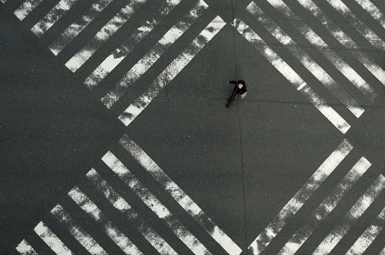 A woman walks through an empty pedestrian crossing in the Ginza shopping district in Tokyo, Friday, April 3, 2020. (AP Photo)