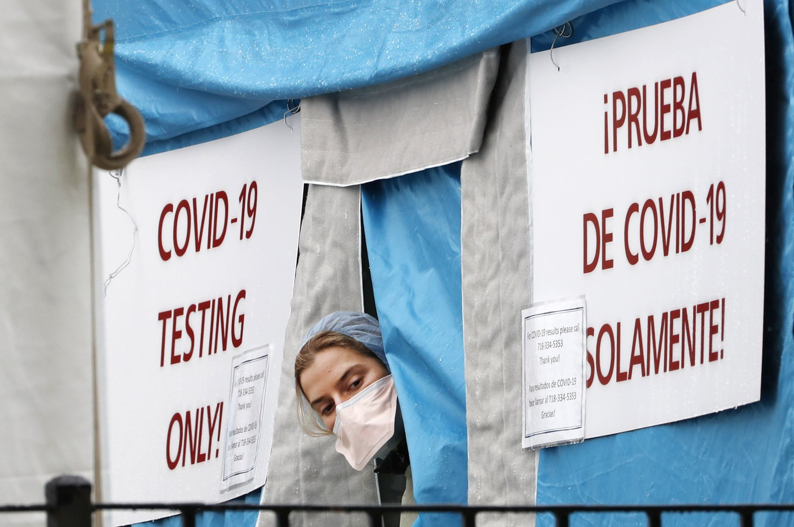 A medical worker sticks her head outside a COVID-19 testing tent set up outside Elmhurst Hospital Center in New York, Saturday, March 28, 2020. (AP Photo)