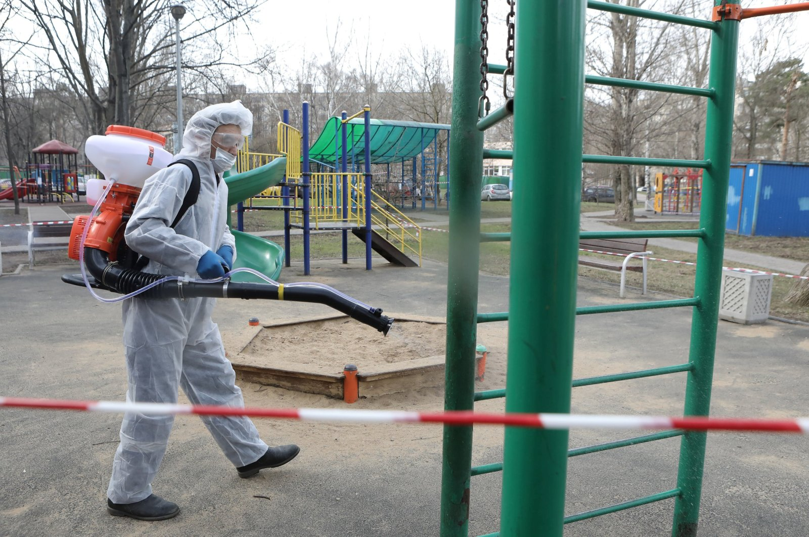 A specialist wearing protective gear sprays disinfectant a playground to prevent the spread of the coronavirus disease (COVID-19) in Moscow, Russia, Sunday, April 5, 2020. (Reuters Photo)