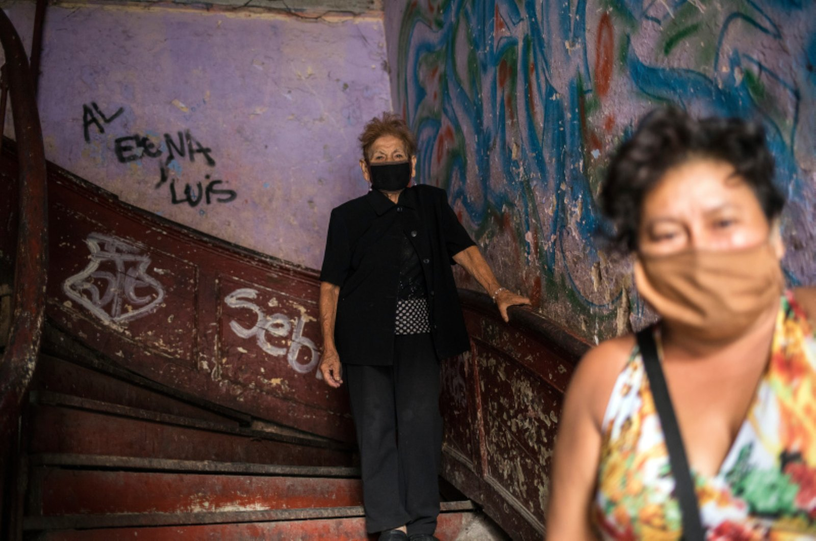 """Maria Isabel Aguinaga, 72, wearing a protective face mask, descends the stairs of her crumbling residential building nicknamed """"Luriganchito"""" after the country's most populous prison, Lima, Peru, March 29, 2020. (AP Photo)"""