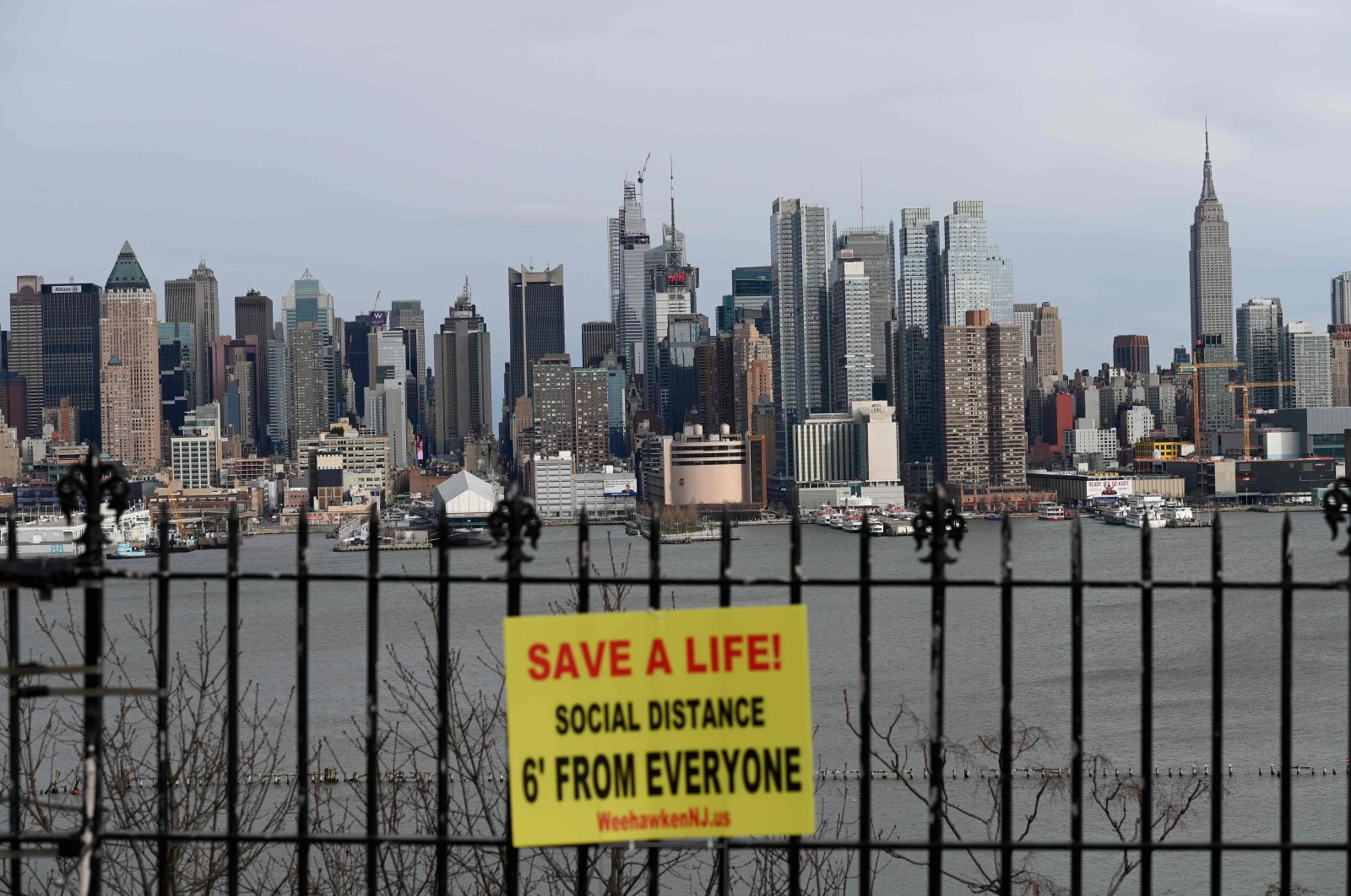 A sign hangs in a park overlooking the Manhattan skyline, as seen from Weehawken, New Jersey, Thursday, April 2, 2020. (AFP Photo)