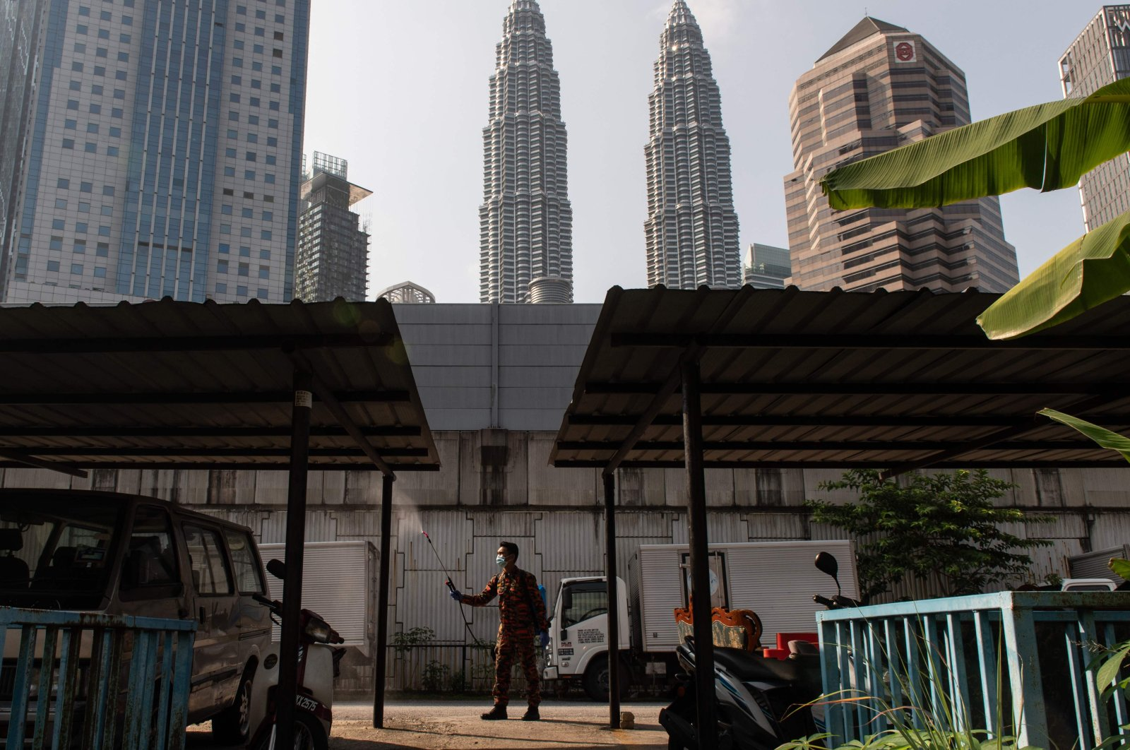 A man sprays disinfectant near a residential area during the Movement Control Order as a preventive measure against the spread of COVID-19, Kuala Lumpur, Malaysia, Tuesday, March 31, 2020. (AFP Photo)