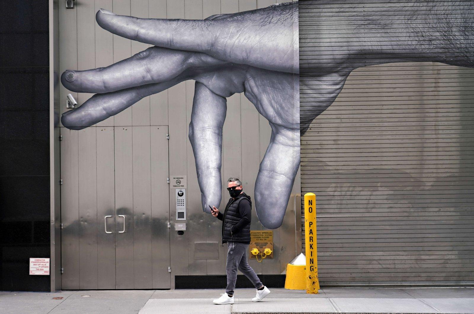 A man wearing a protective mask walks by street art amid the coronavirus pandemic, New York City, Sunday, April 5, 2020. (AFP Photo)