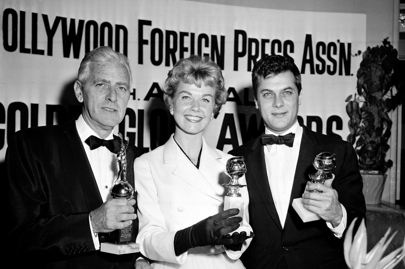 In this Feb. 26, 1958 file photo, actress Doris Day, center, Tony Curtis, right, and Buddy Adler pose with their awards presented to them by the Hollywood Foreign Press Association at its annual awards dinner in the Cocoanut Grove in Los Angeles. (AP Photo)