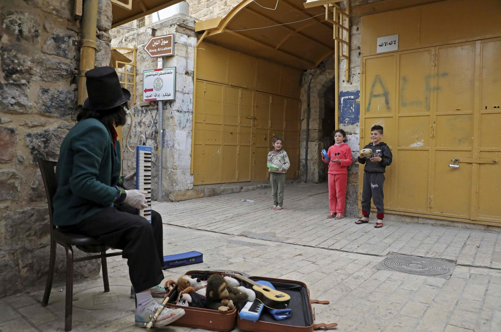 A Palestinian artist, dressed as a clown, plays music near Palestinian children in the divided West Bank town of Hebron, Tuesday, March 31, 2020. (AFP Photo)