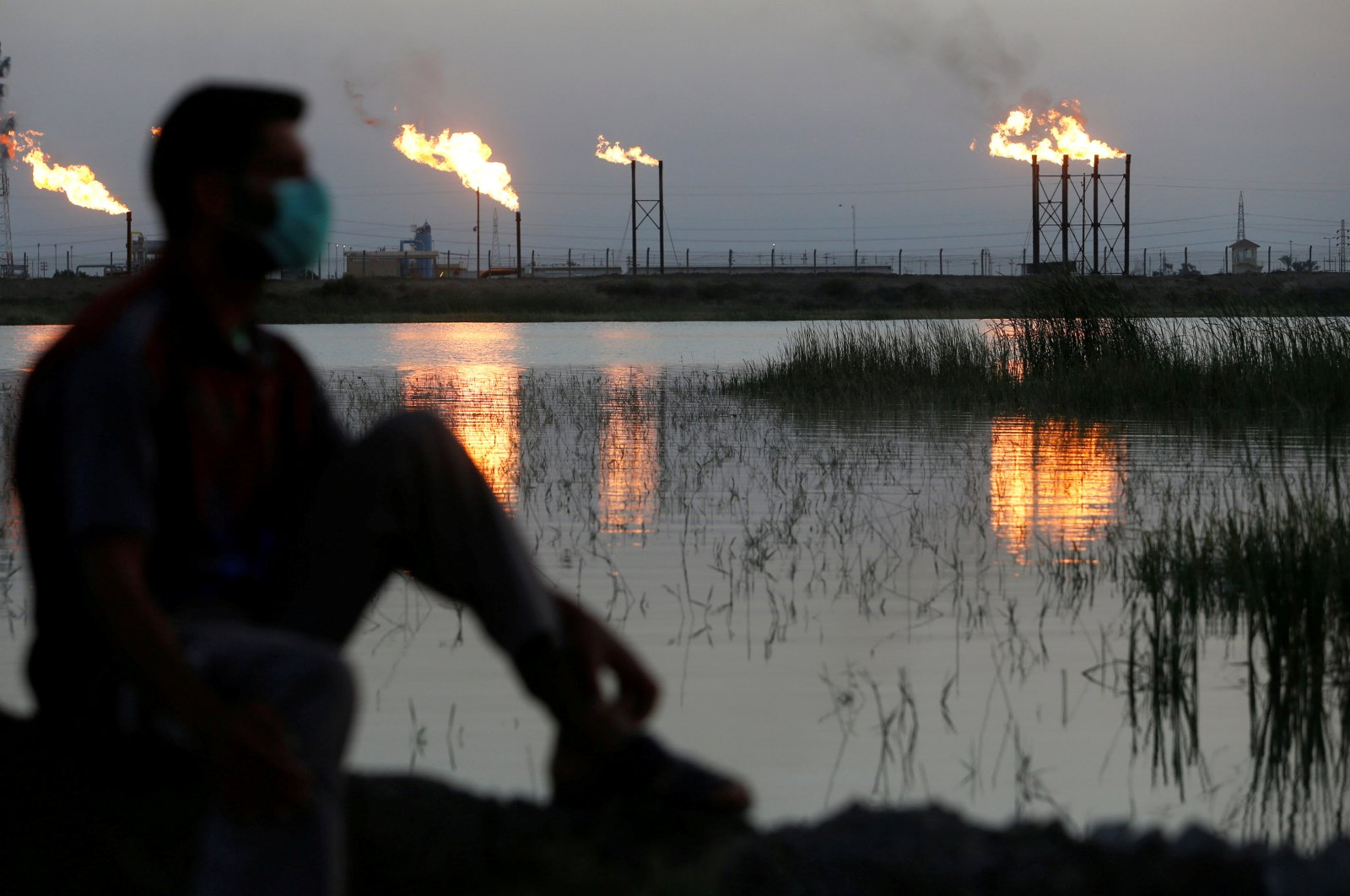 Flames emerge from flare stacks at Nahr bin Umar oil field, as a man is seen wearing a protective face mask, following the outbreak of the coronavirus, north of Basra, Iraq, March 9, 2020. (Reuters Photo)