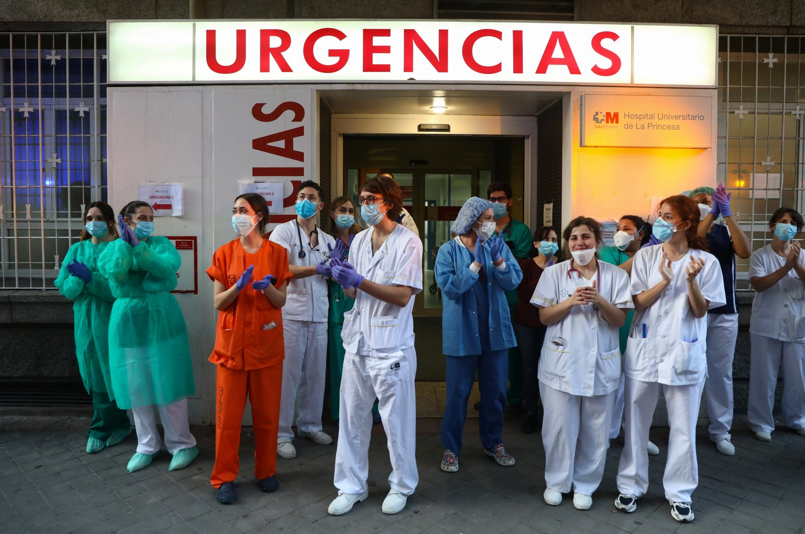 Medical staff from La Princesa hospital react as neighbours applaud from their balconies in support for healthcare workers, Madrid, April 5, 2020. (REUTERS Photo)