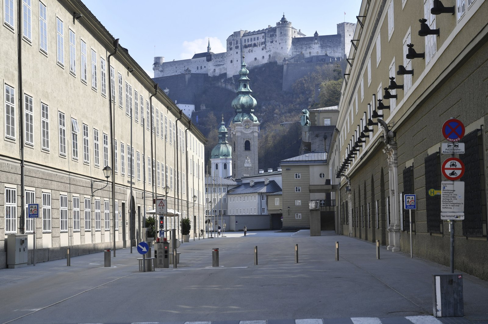 """The famous Hofstallgasse with the """"Festung Hohensalzburg"""" in the background during rush hour in Salzburg, Austria, Friday, April 3, 2020. (AP Photo)"""