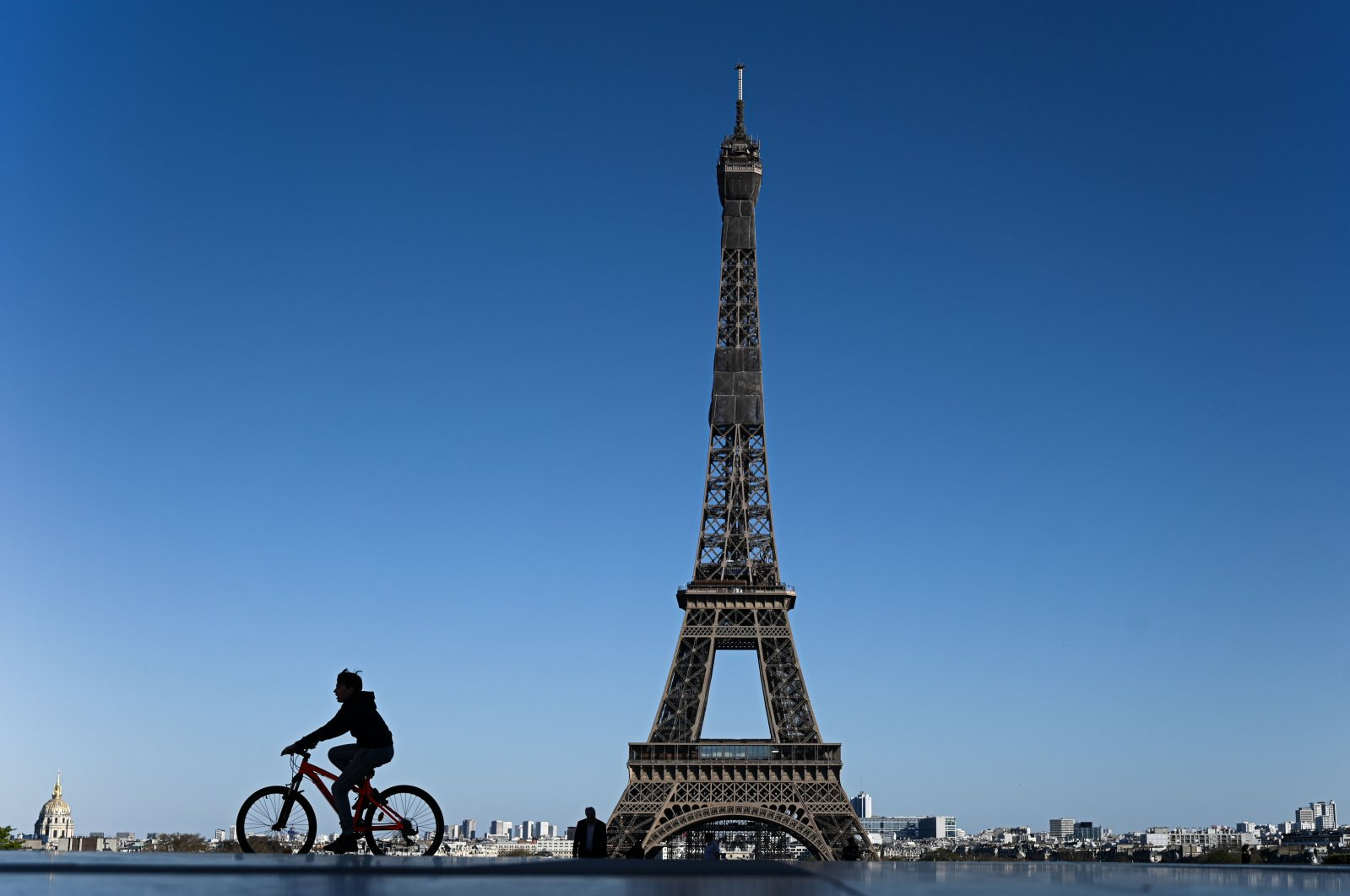 A boy rides his bicycle past the Eiffel Tower in Paris on Sunday, April 5, 2020, the 20th day of a lockdown in France aimed at curbing the spread of COVID-19. (AFP Photo)