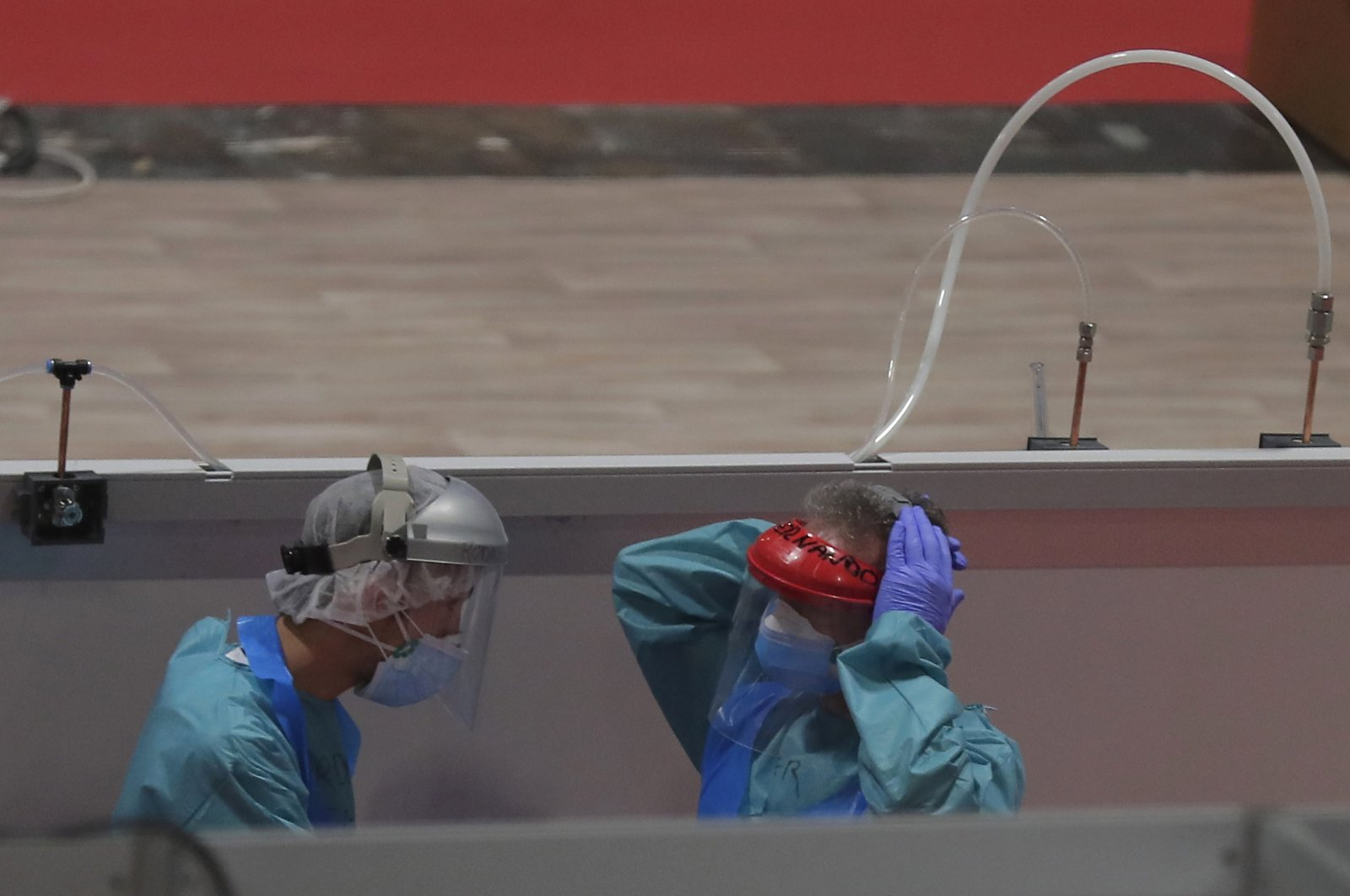 Medical workers talk at a temporary field hospital set in Ifema convention and exhibition in Madrid, Spain, April. 2, 2019. (AP Photo)