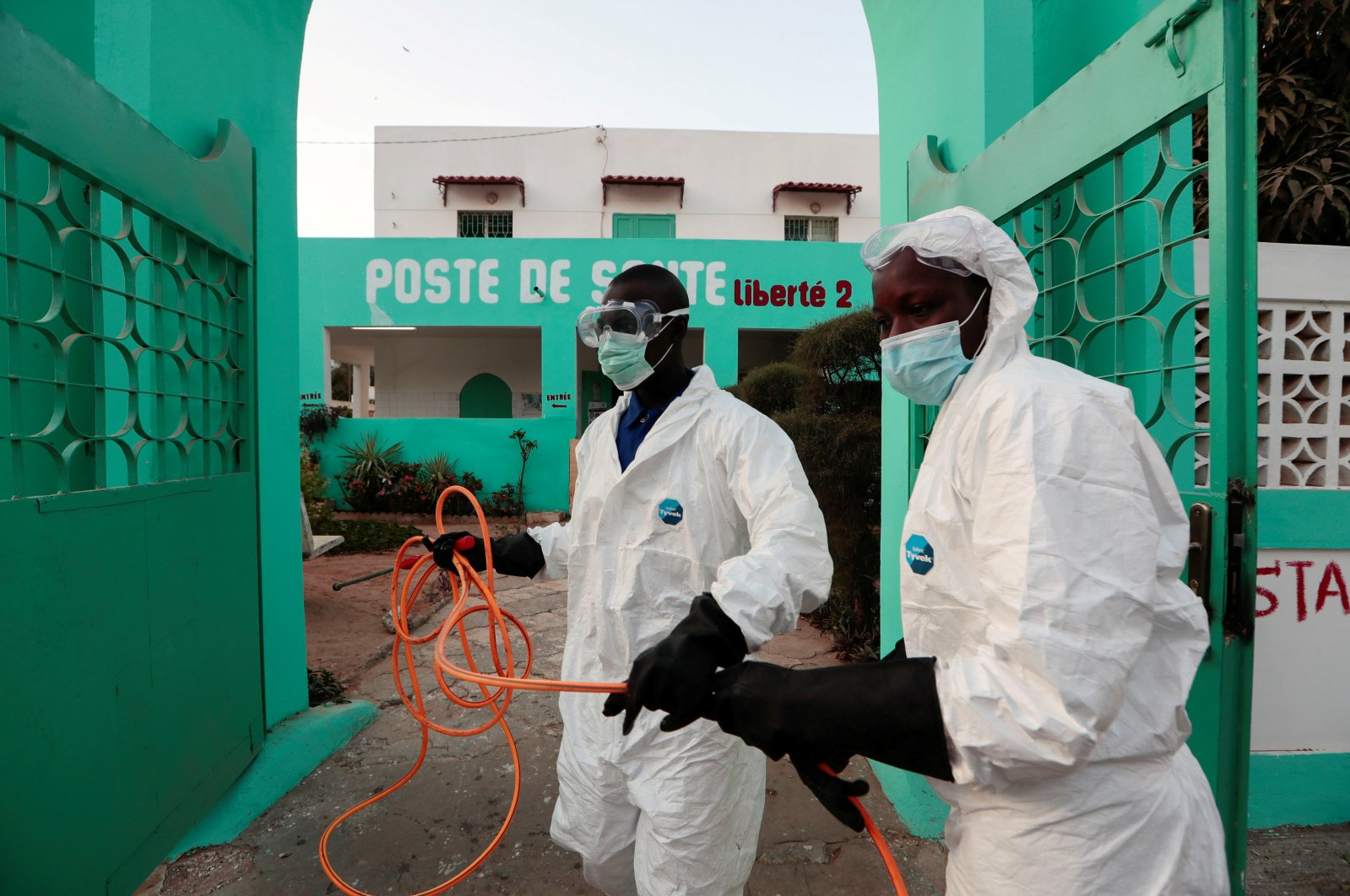 Members of local hygiene services wear protective suits and face masks, as they prepare to disinfect a health center to stop the spread of COVID-19 in Dakar, Senegal, Wednesday, April 1, 2020. (Reuters Photo)