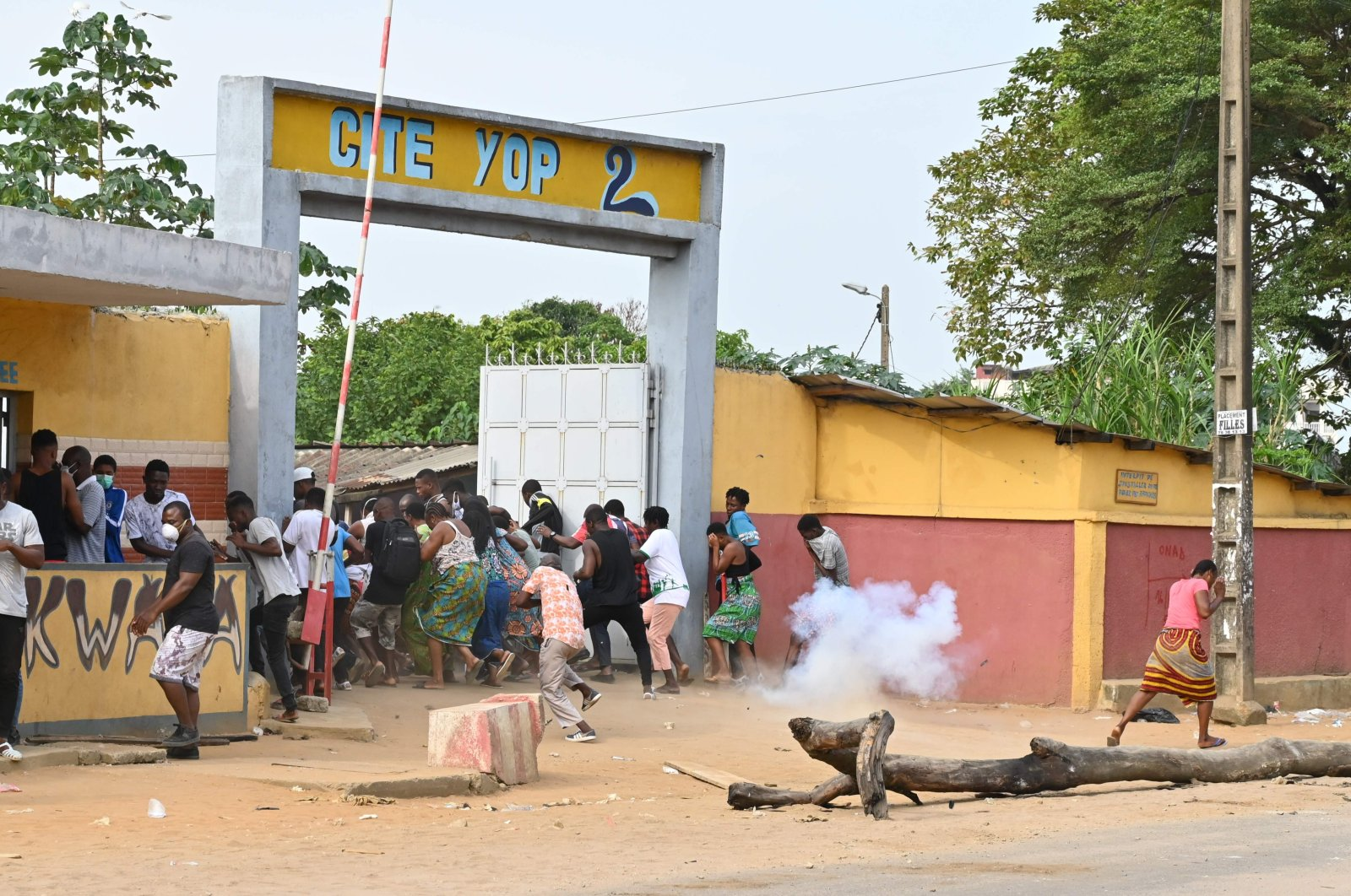 Demonstrators run away during clashes with Ivory Coast anti-riot police at a demonstration against the construction of a COVID-19 coronavirus screening center, Yopougon, Monday, April 6, 2020. (AFP Photo)