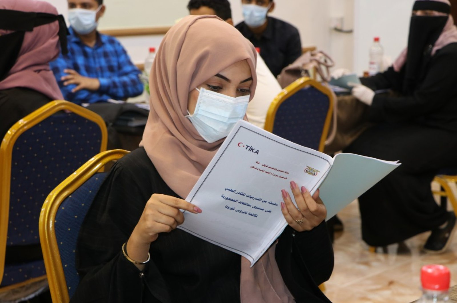 A trainee reads a pamphlet during a training session at the workshop in Aden, Yemen, Monday, April 6, 2020. (COURTESY OF TİKA)