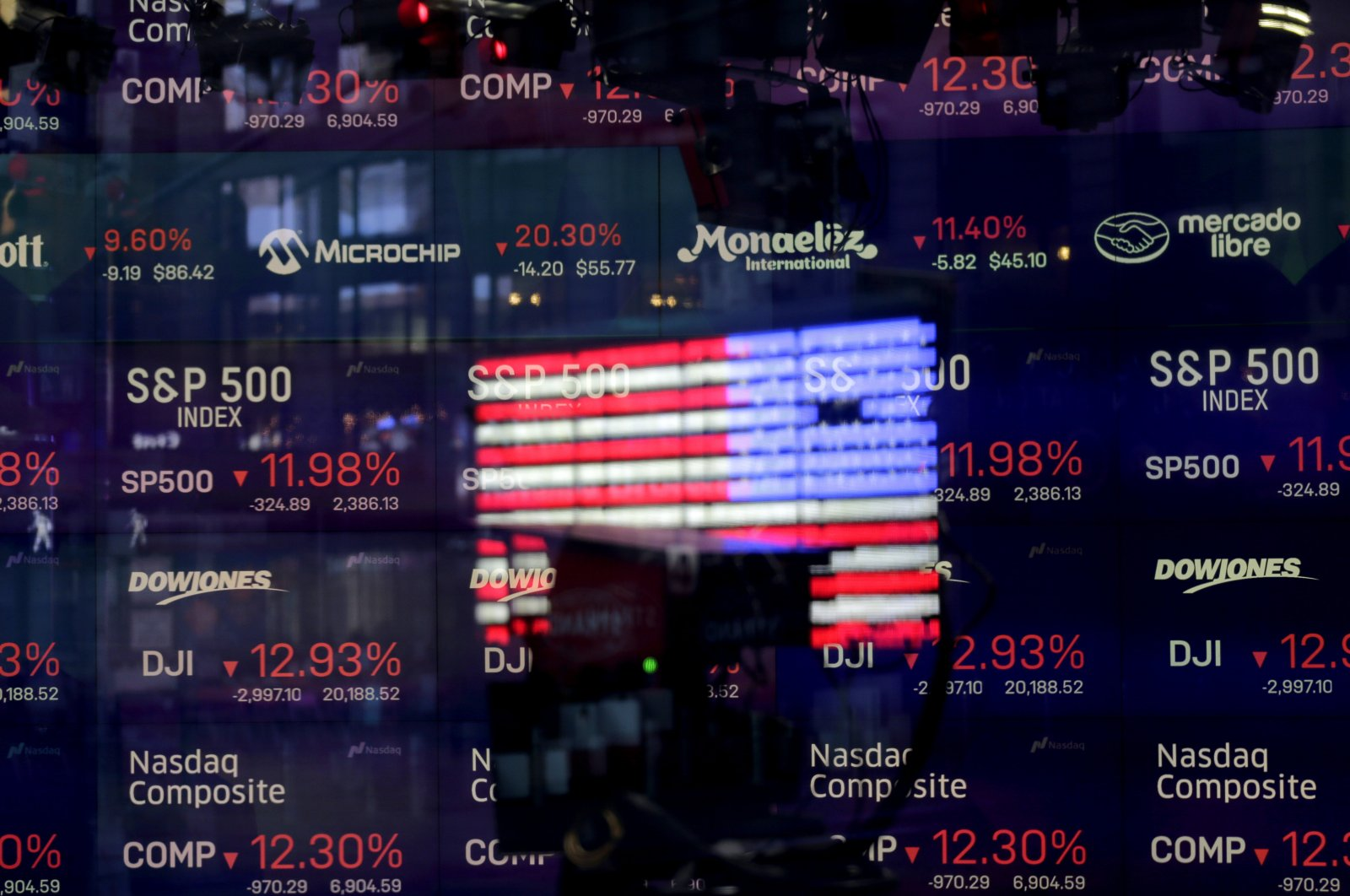 The U.S. flag is reflected in the window of the Nasdaq studio, which displays indices and stocks down, in Times Square, New York City, March 16, 2020. (AP Photo)