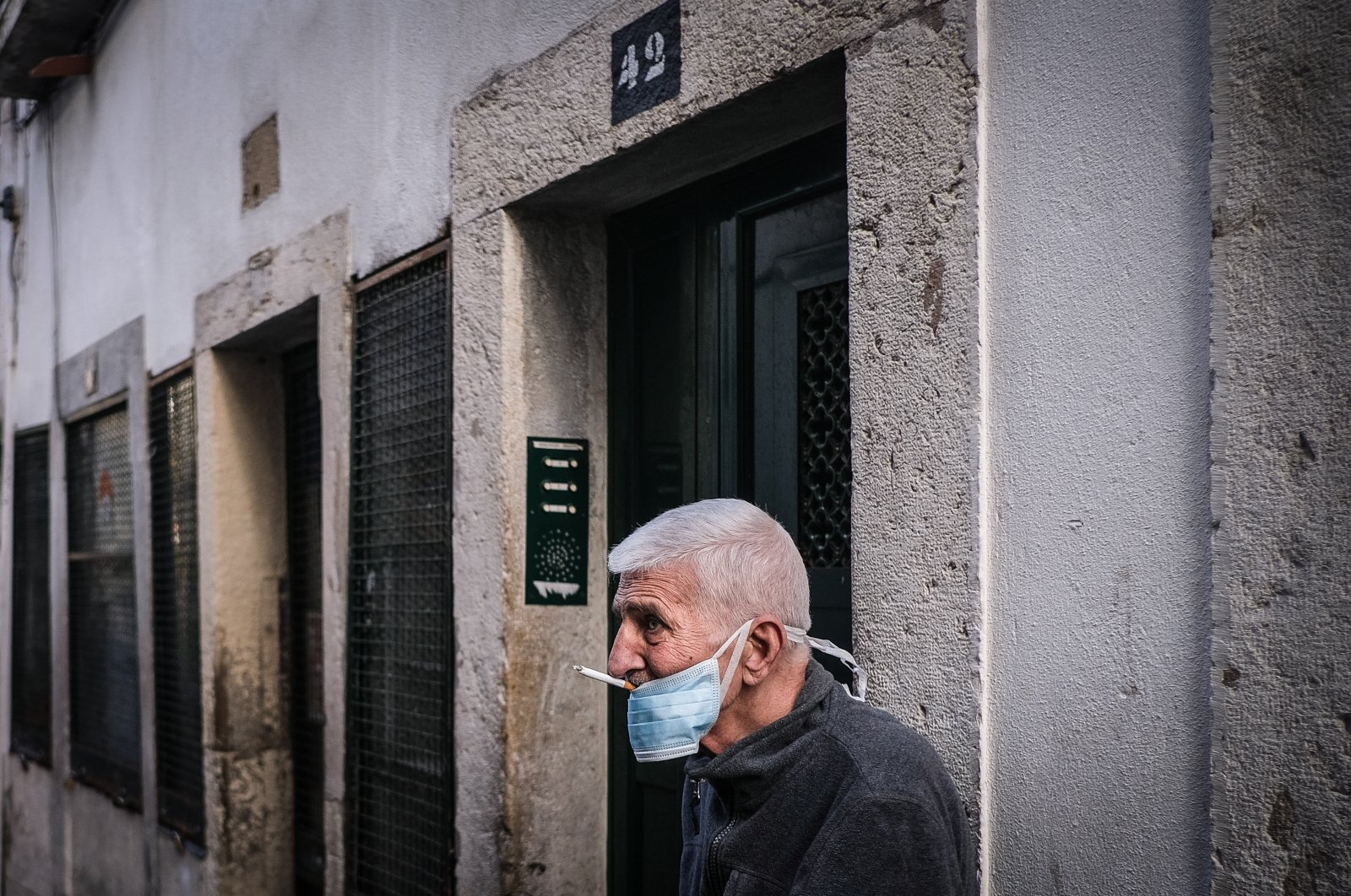 A man wearing a protective mask smokes a cigarette in the Alfama neighborhood in Lisbon, Portugal, Friday, April 3, 2020. (EPA Photo)