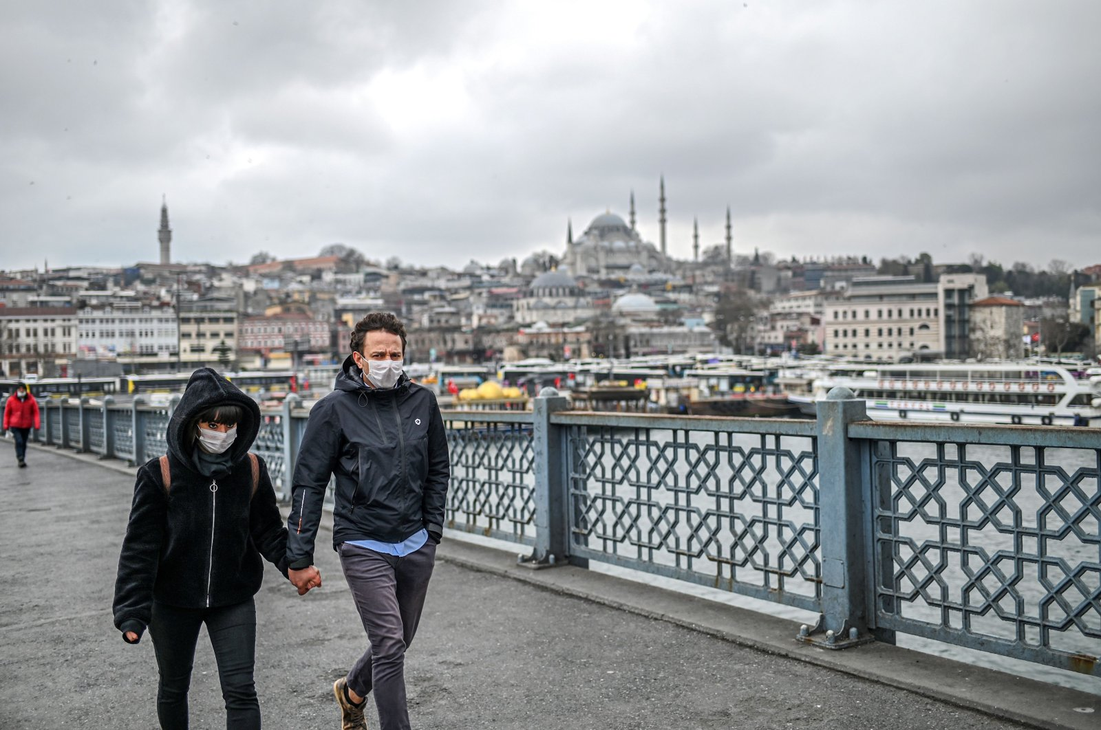 A couple holding hands and wearing face masks walk across the empty Galata bridge, on Wednesday, April 1, 2020 (AFP Photo)