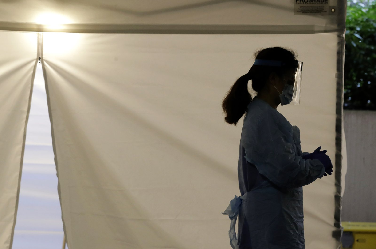 In this March 13, 2020, file photo, a nurse at a drive-up coronavirus testing station set up by the University of Washington Medical Center wears a face shield and other protective gear as she waits by a tent in Seattle. (AP Photo)
