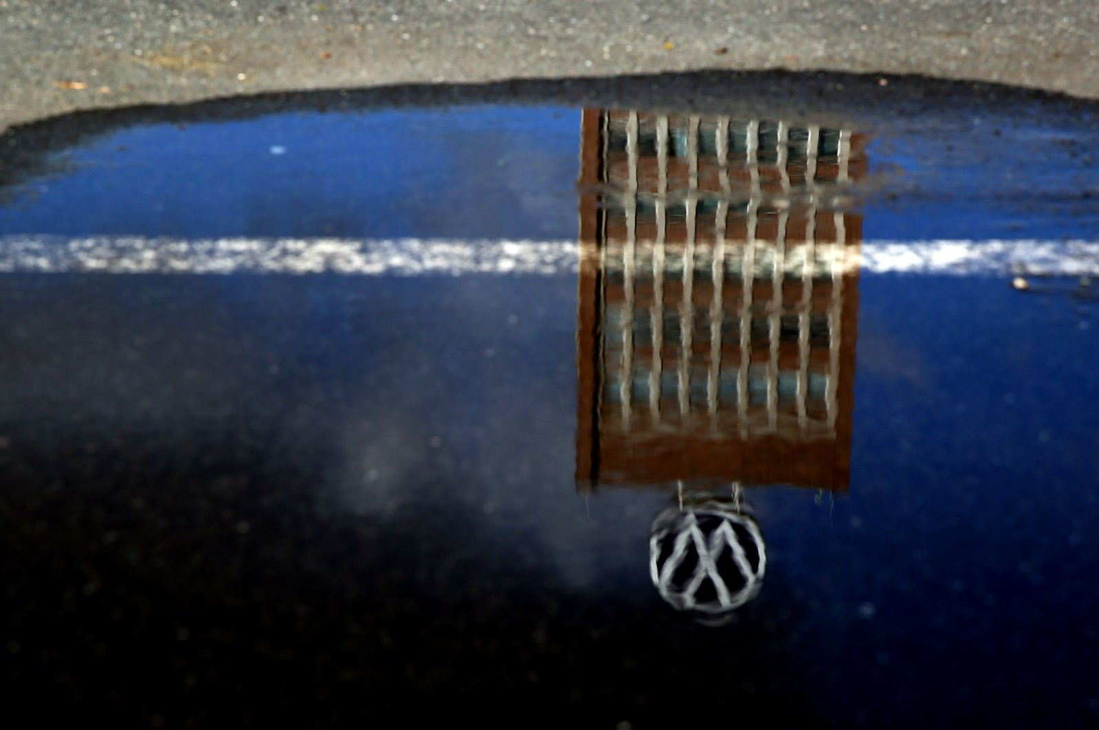 The headquarters of German carmaker Volkswagen (VW) is reflected in a puddle in Wolfsburg, Germany, Feb. 28, 2020. (AFP Photo)
