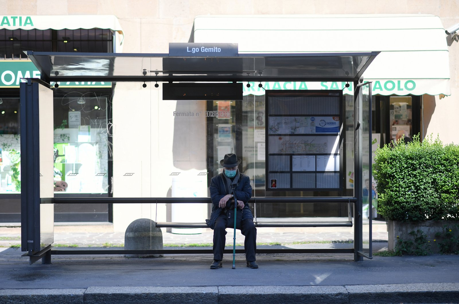 A man wearing a face mask sits at a bus stop, as the spread of the coronavirus continues, in Milan, Italy, Monday, April 6, 2020. (Reuters Photo)