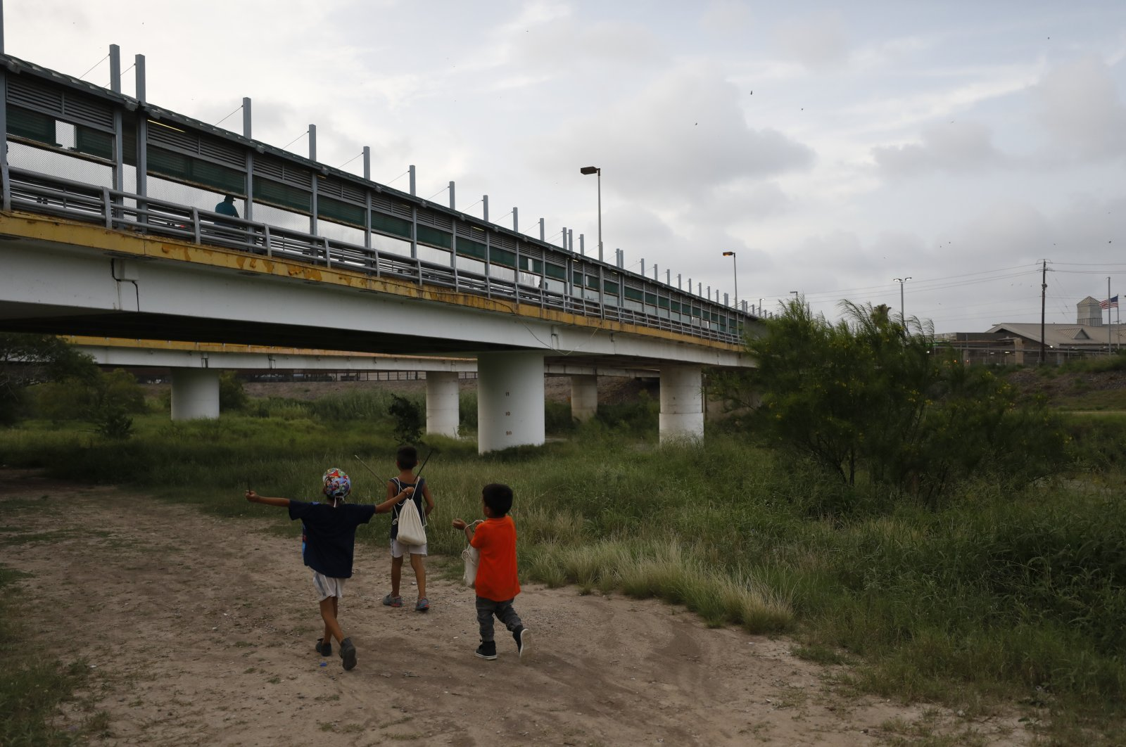 In this June 26, 2019 file photo, migrant children walk with their families along the Rio Grande, as pedestrian commuters use the Puerta Mexico bridge to enter Brownsville, Texas, seen from Matamoros, Tamaulipas state, Mexico. (AP Photo)