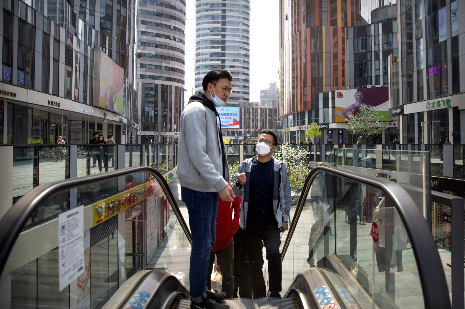 People wear face masks as they ride an escalator, Beijing, China, Tuesday, April 7, 2020. (AP Photo)
