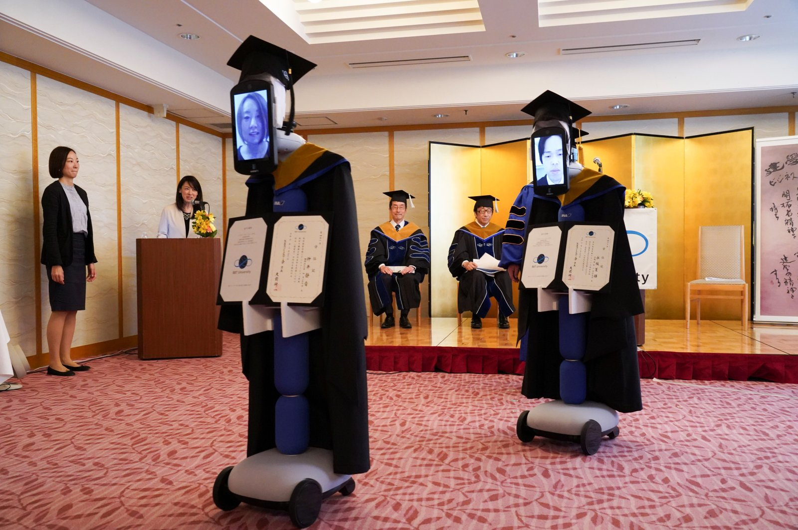 Ipads attached to 'newme' robots replacing graduating students' presence at a ceremony, wear graduation gowns and hats in Tokyo, Japan, Saturday, March 28, 2020. (Reuters Photo)