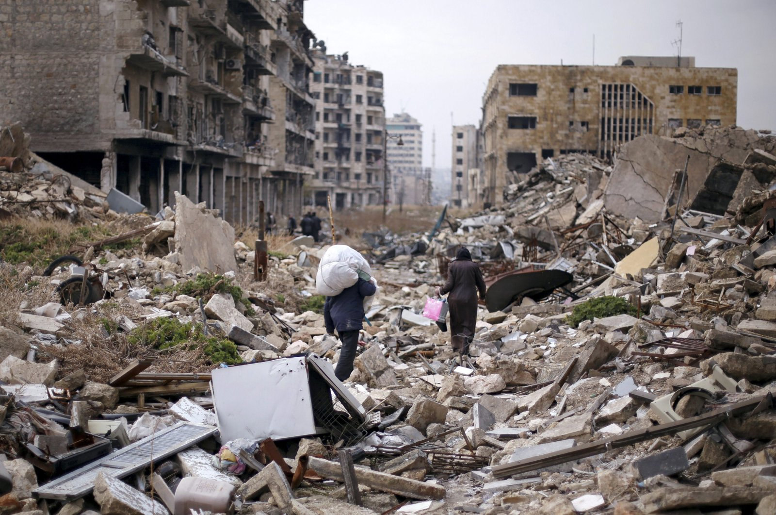 People walk amid the rubble as they carry belongings that they collected from their houses in the Assad regime controlled area of Aleppo, Syria, December 17, 2016. (REUTERS Photo)