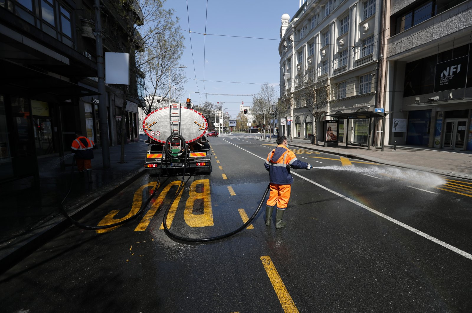 Workers clean the street during a curfew set up to help prevent the spread of the coronavirus in downtown Belgrade, Serbia, Saturday, April 4, 2020. (AP)