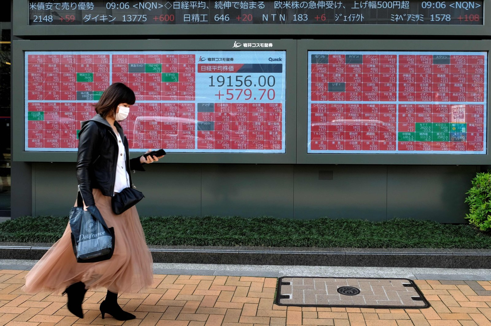 A pedestrian walks past a quotation board displaying share prices of the Tokyo Stock Exchange in Tokyo on April 7, 2020. (AFP Photo)