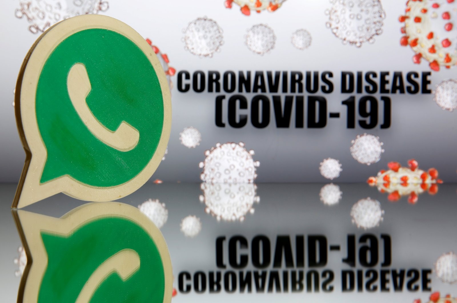 A 3D-printed Whatsapp logo embellishes a coronavirus disease (COVID-19) sign in this illustration from March 19, 2020. (Reuters Photo)