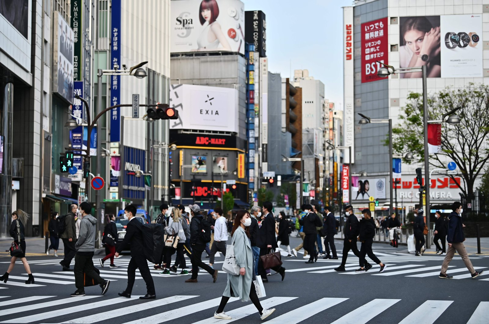 People cross a street in Tokyo's Shinjuku district, April 7, 2020. (AFP Photo)