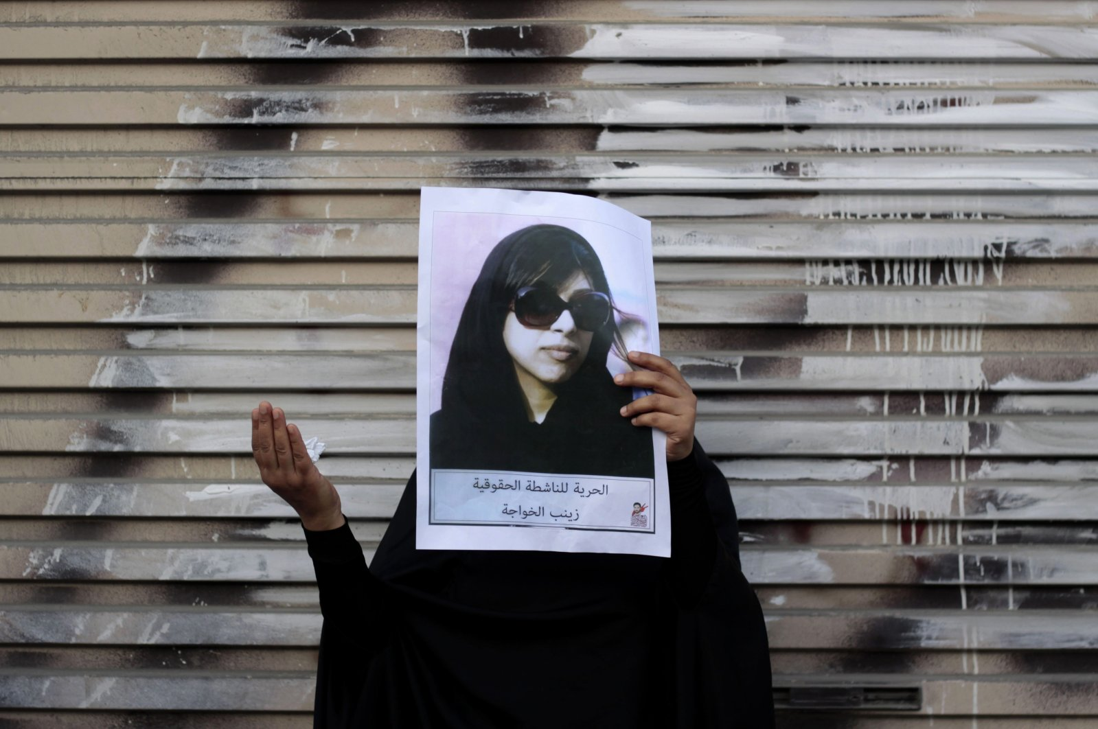 In this March 28, 2013 file photo, a Bahraini anti-government protester holds up a picture of jailed opposition human rights activist Zainab al-Khawaja as she participates in a prayer for al-Khawaja's freedom after a march in Malkiya, Bahrain.  April 16, 2015. (AP Photo)