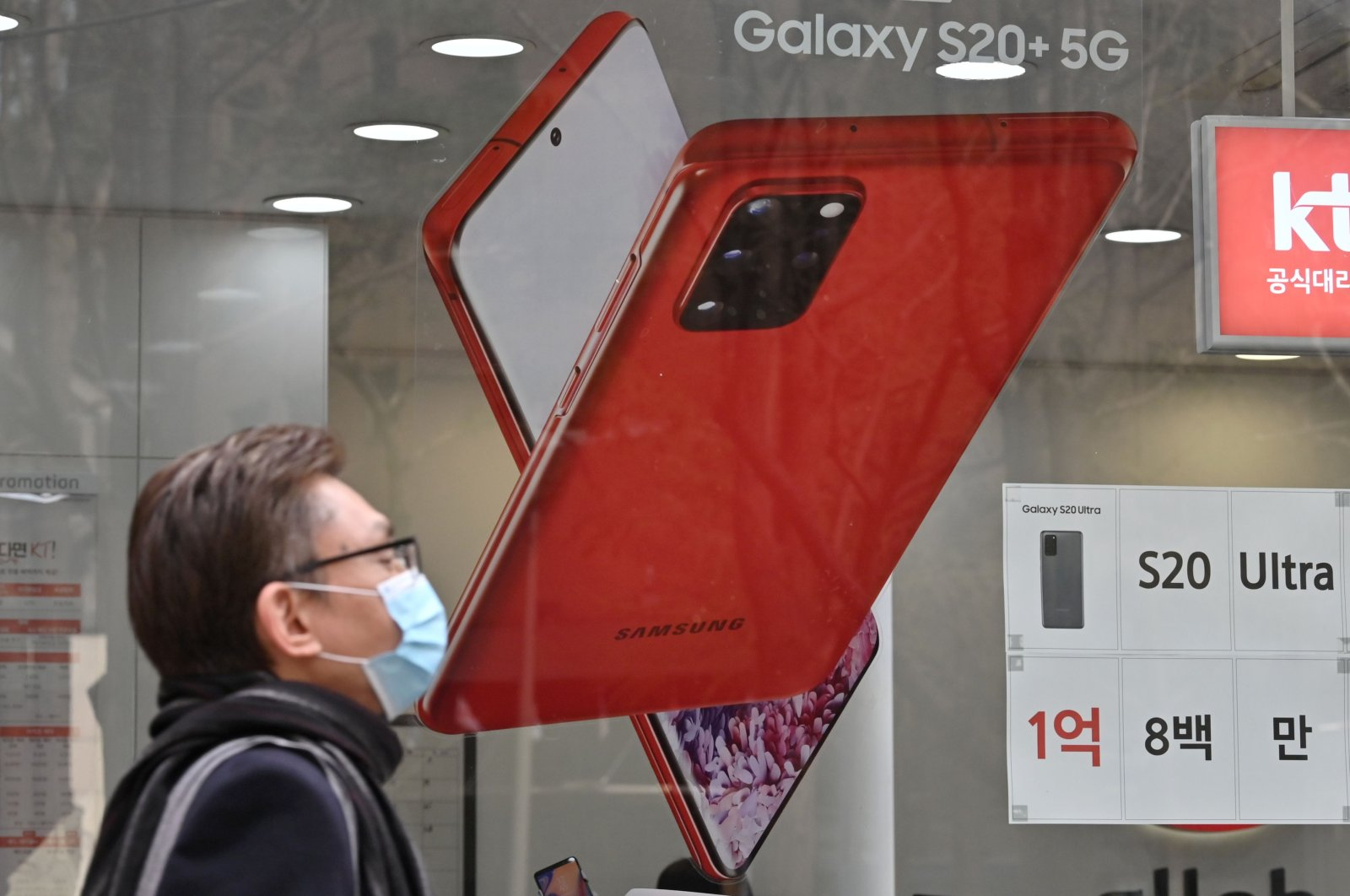 A man walks past an advertisement for the Samsung Galaxy S20 5G smartphone at a telecom shop in Seoul, Tuesday, April 7, 2020. (AFP Photo)