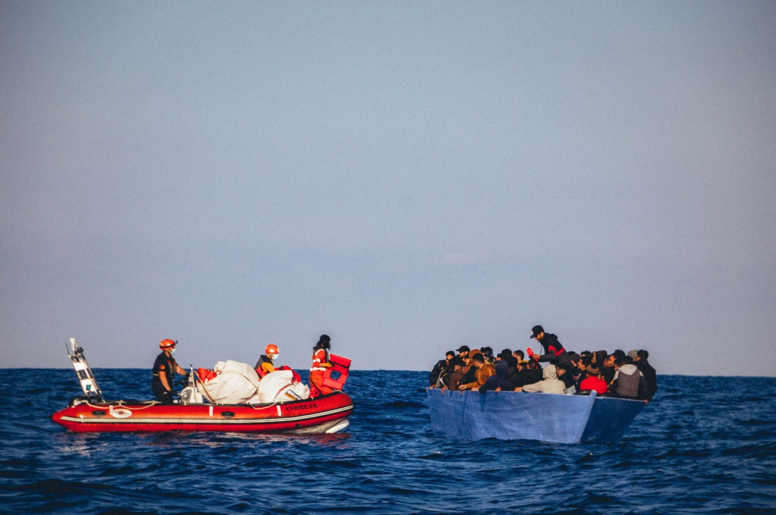 Members of Sea Eye on a rubber boat rescue people from a small wooden boat in distress off the Libyan coast, Monday, April 6, 2020. (AFP Photo)
