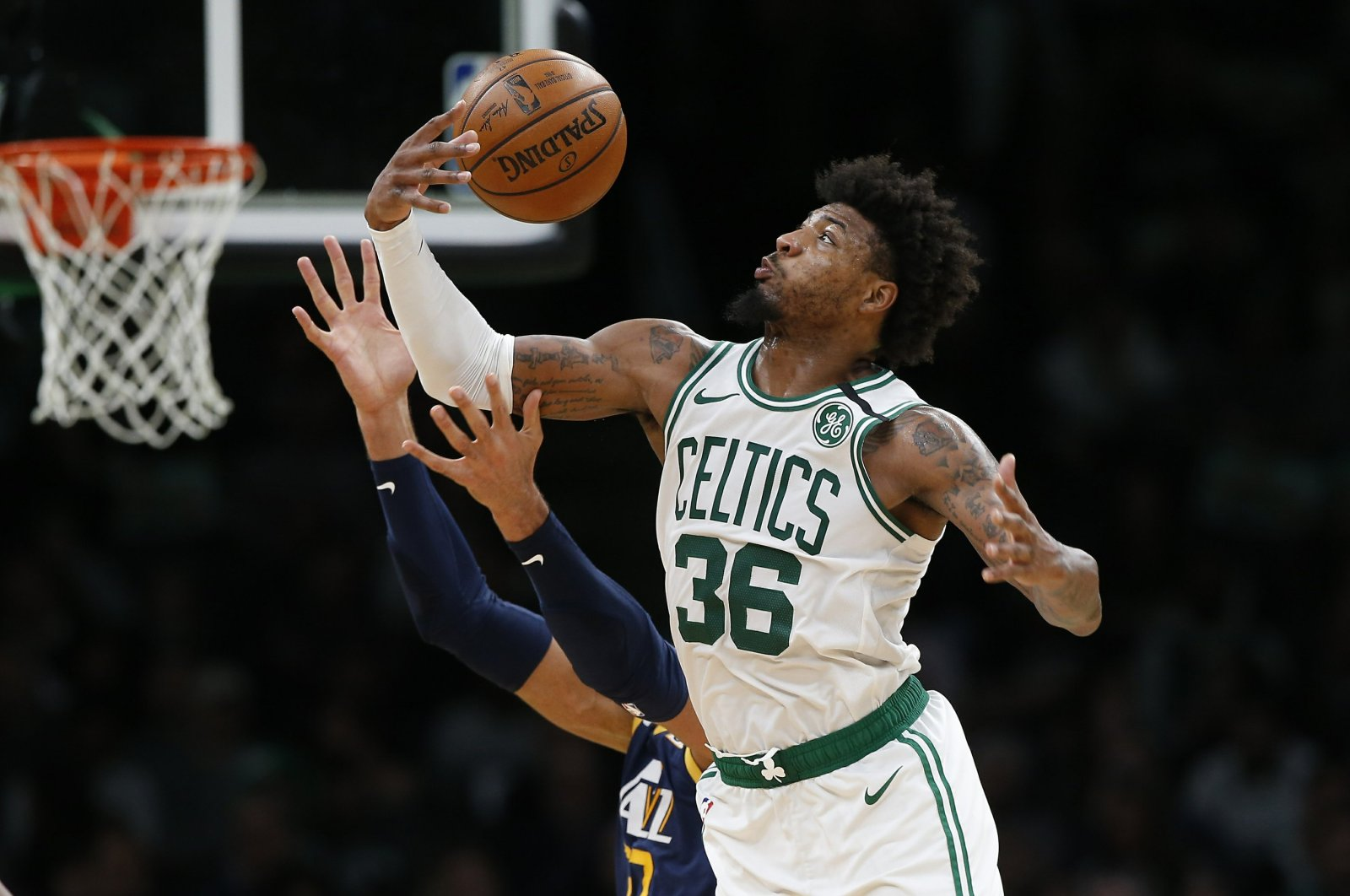 Boston Celtics' Marcus Smart (36) gathers in a rebound against the Utah Jazz during an NBA game, in Boston, March 6, 2020. (AP Photo)