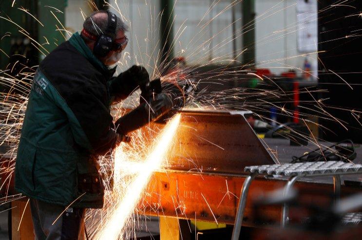 A worker grinds metal at the machine-building company Zemmler Siebanlagen in Massen, Germany, March 22, 2018. (Reuters Photo)