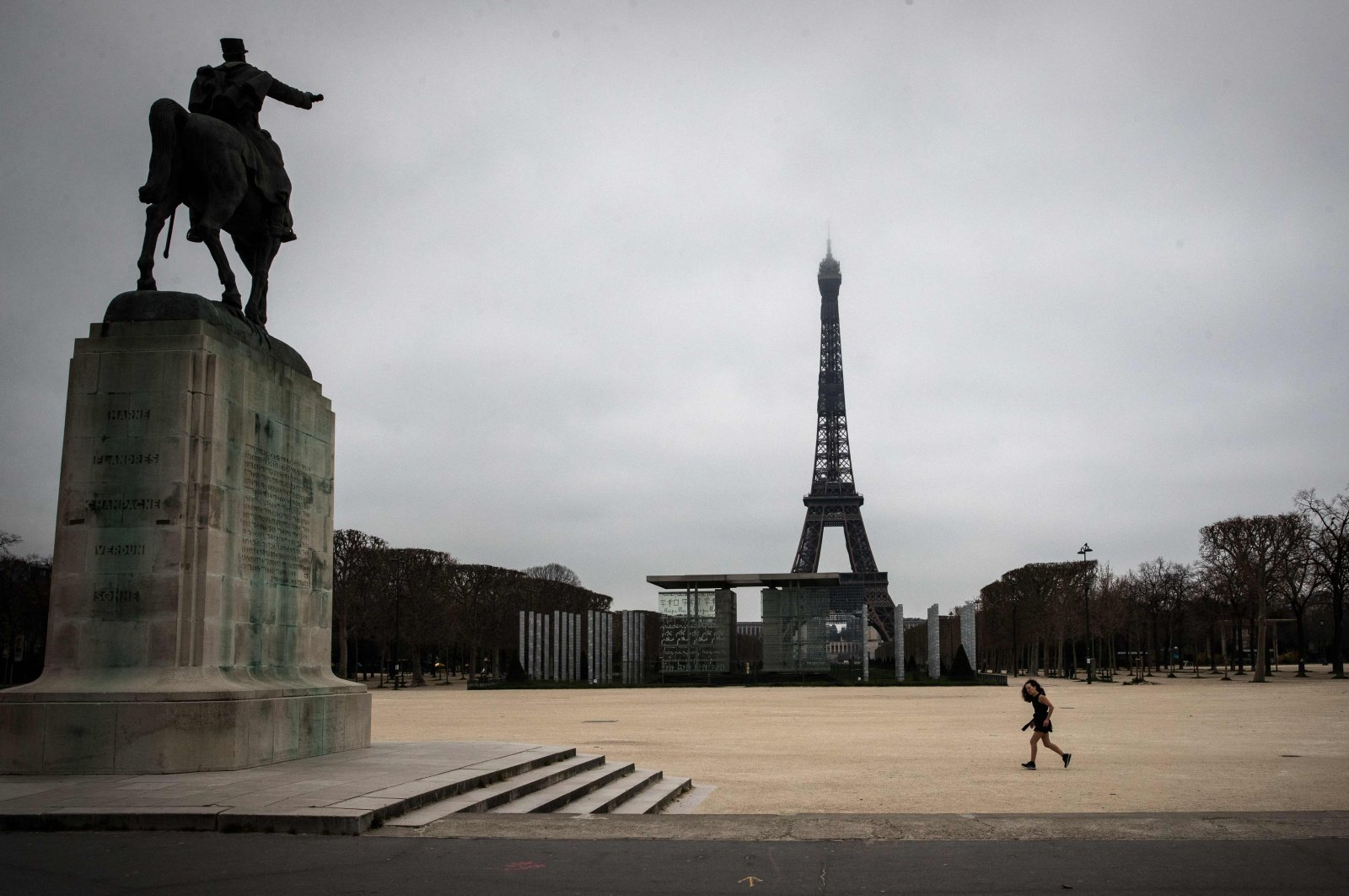 A jogger runs in the Champs de Mars as a strict lockdown comes into in effect in France to stop the spread of COVID-19, Paris, France, March 21, 2020 . (AFP Photo)