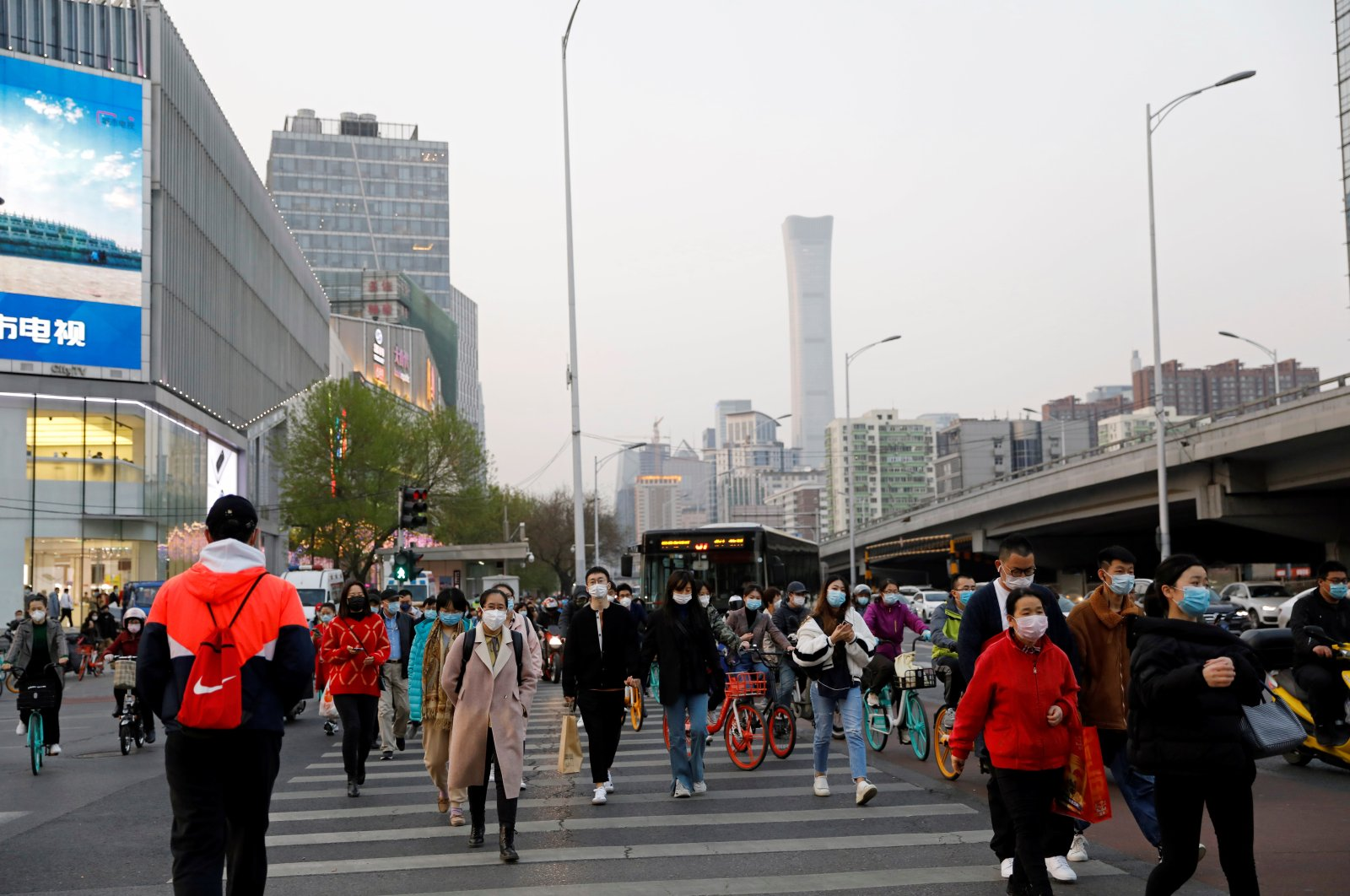 People wearing protective face masks cross a street, following an outbreak of the coronavirus disease, in Beijing, China, Tuesday, April 7, 2020. REUTERS