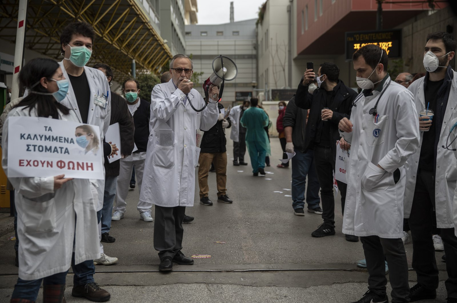 A doctor speaks through a loudspeaker during a protest at Evagelismos hospital during the World Health Day, Athens, Tuesday, April 7, 2020. (AP Photo)