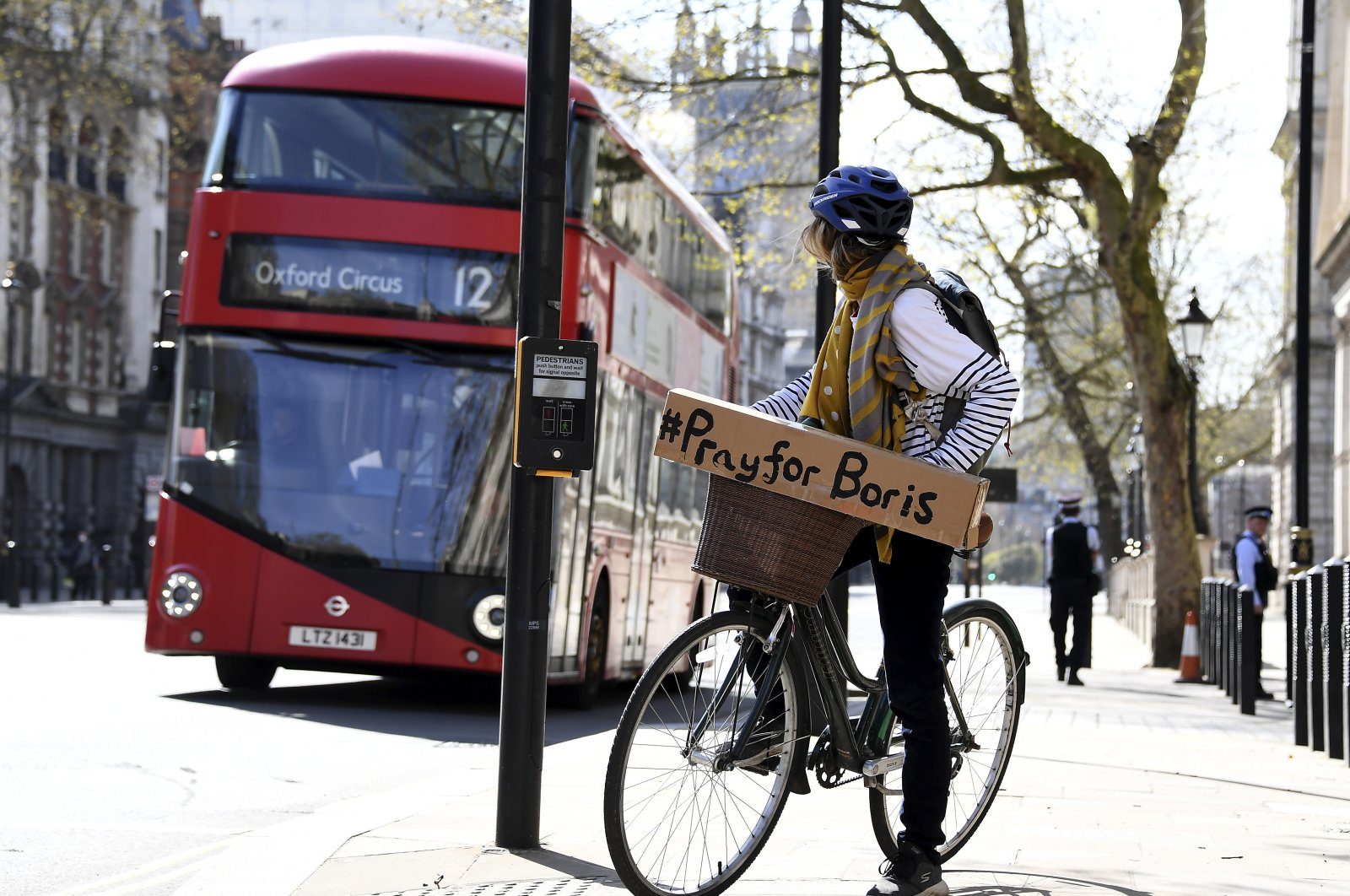 A woman shows a sign on her bicycle as British Prime Minister Boris Johnson is in intensive care fighting the coronavirus in London, Tuesday, April 7, 2020. (AP Photo)