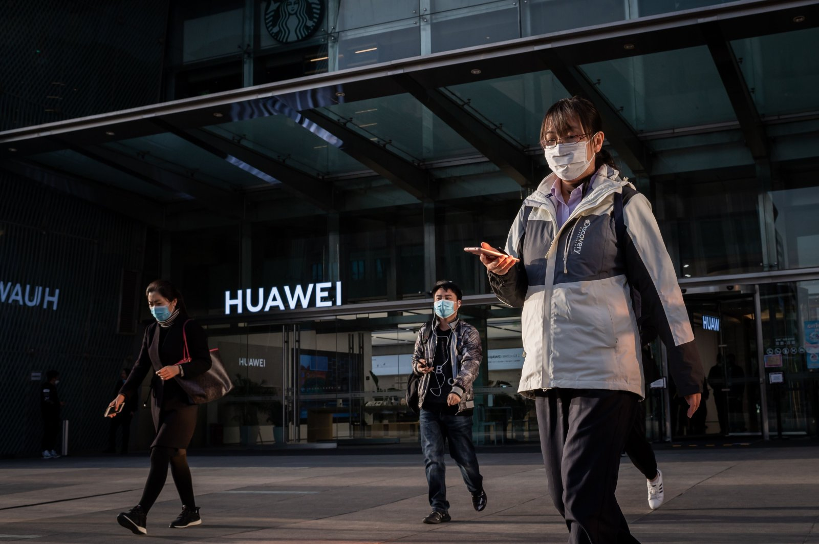 People wearing face masks as a preventive measure against COVID-19 walk outside a shopping mall past a Huawei shop in Beijing, Wednesday, April 1, 2020. (AFP Photo)