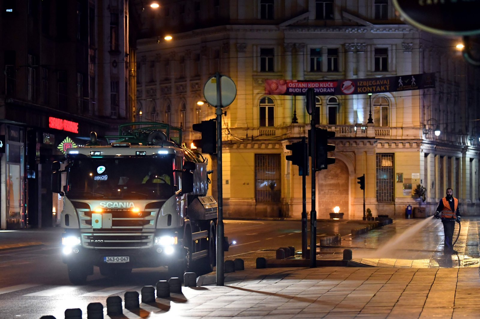 Bosnian sanitation workers use curfew hours to wash streets with water and sanitizing solution, in Sarajevo, late on April 4, 2020. (AFP Photo)